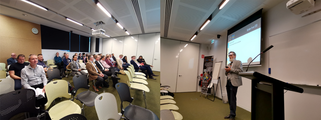 Graham standing before a projection of a Powerpoint slide on the right with NIF Fellows and Associates seated seminar style on the left