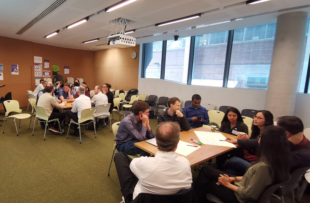 NIF Fellows seated in groups focusing on a brainstorming activity